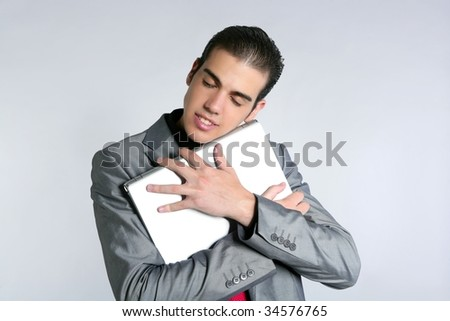 Businessman young embracing computer, hug laptop love his work - stock photo