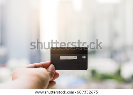 Businessman young man hand show credit card outdoor on city background.