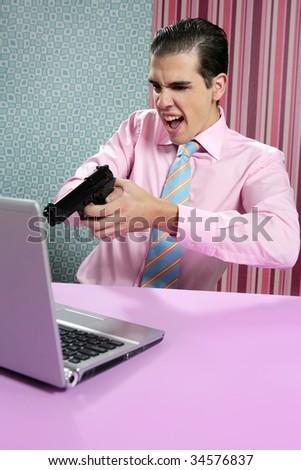 businessman young shooting handgun with computer pink bacground - stock photo