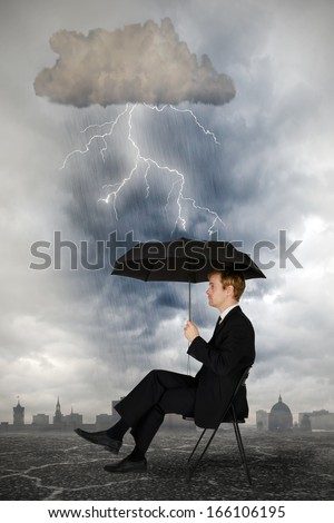Businessmann sits with an umbrella under a thundercloud with lightning