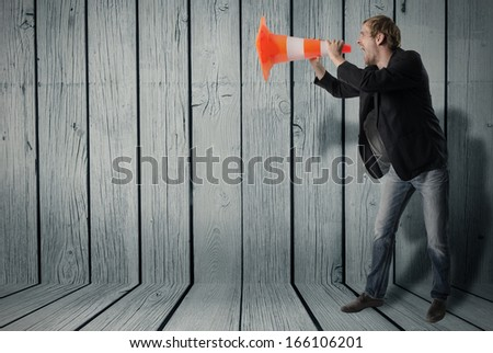 Businessmann uses a warning cone as a megaphone and shouts through - stock photo