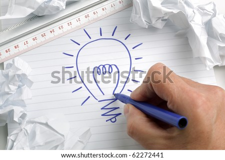 Businessmans hand drawing a light bulb, concept for brainstorming and inspiration - stock photo