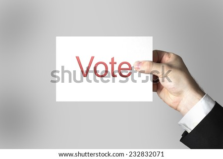 businessmans hand holding card vote