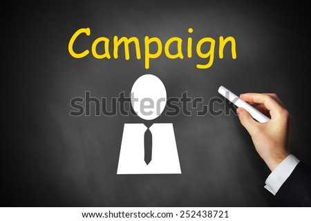 businessmans hand writing campaign on black chalkboard - stock photo