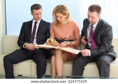 Businessmen and a woman reading a newspaper sitting on a white couch - stock photo