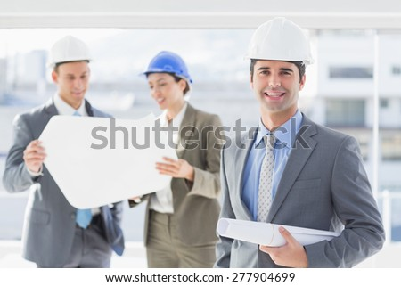 Businessmen and a woman with hard hats and holding blueprint in the office - stock photo