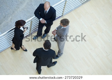 Businessmen and businesswoman standing together by railing - stock photo