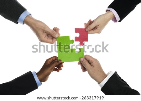 Businessmen and businesswomen holding jigsaw - stock photo