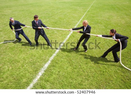 Businessmen and businesswomen playing tug of war - stock photo