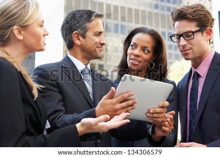 Businessmen And Businesswomen Using Digital Tablet Outside - stock photo