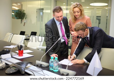 Businessmen and secretary make changes to documents in conference hall - stock photo