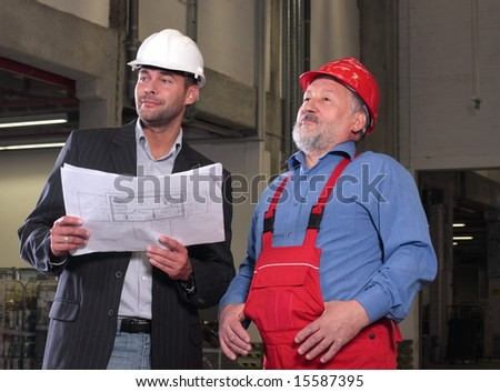 businessmen and  senior worker, wearing hardhats looking at a set of blueprints and discussing a construction project.
