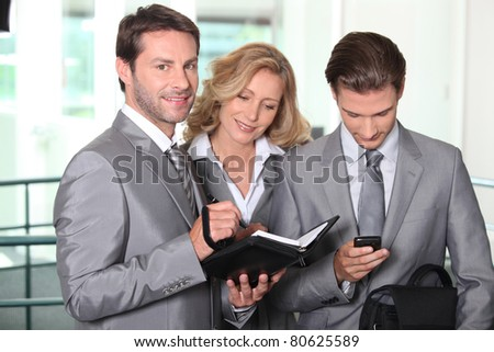 Businessmen and woman checking diary - stock photo
