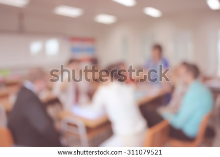 Businessmen and women blur in after work conference - stock photo