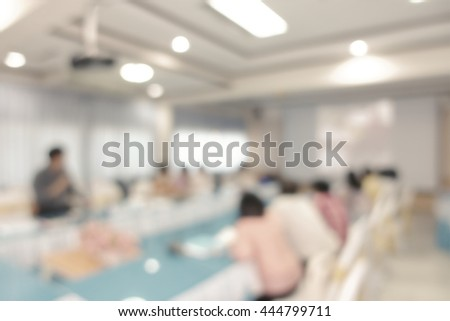 Businessmen and women blur in conference room presenting new product - stock photo