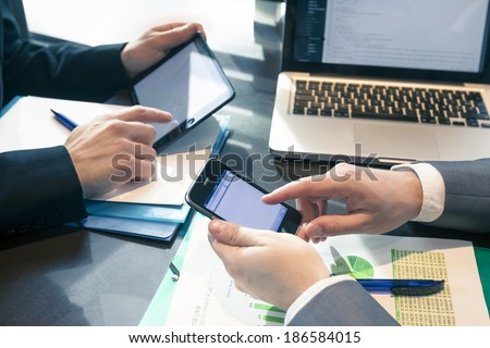 Businessmen at meeting presenting charts on smartphone, tablet and laptop - stock photo