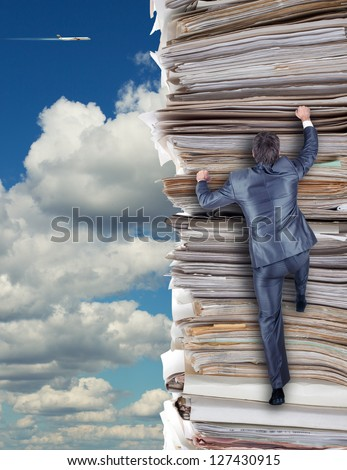 Businessmen climbing up a pile of documents - stock photo