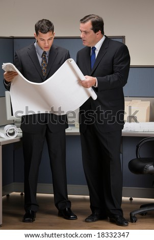 Businessmen collaborating over blueprints in cubicle - stock photo