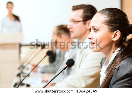 businessmen communicate at the conference, sitting at the table, on the table microphones and documents