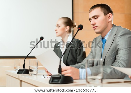 businessmen communicate at the conference, sitting at the table, on the table microphones and documents - stock photo