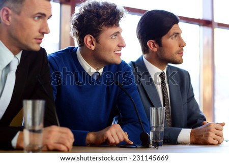 Businessmen communicate at the conference, sitting at the table with microphones - stock photo
