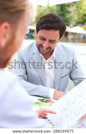 Businessmen deciding menu at sidewalk cafe - stock photo