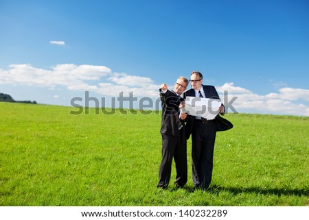 Businessmen discussing a building plan or blueprint standing in the middle of a lush green field pointing to a possible site to locate the building
