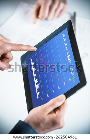 Businessmen discussing an analytical business graph on a tablet pc in a teamwork, brainstorming or planning and strategy concept - stock photo