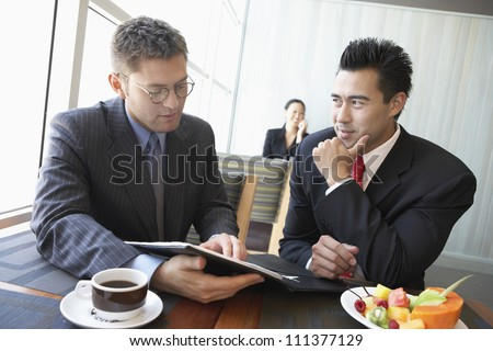 Businessmen discussing contract in restaurant with woman in the background - stock photo