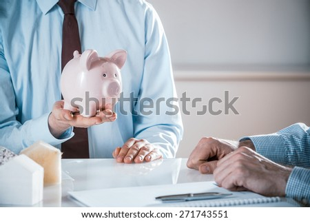 Businessmen discussing house costs and funding with a client holding a piggy bank alongside insulation samples while the engineer or architect takes notes in a savings and achievement concept - stock photo