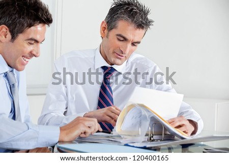 Businessmen discussing paperwork at a meeting in office - stock photo