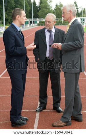 Businessmen discussing their business on a race track. - stock photo