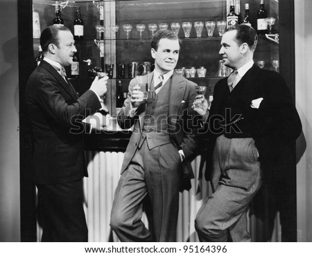 Businessmen drinking together at bar - stock photo