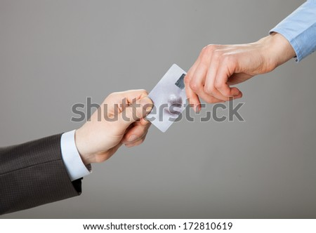 Businessmen exchanging credit card - stock photo