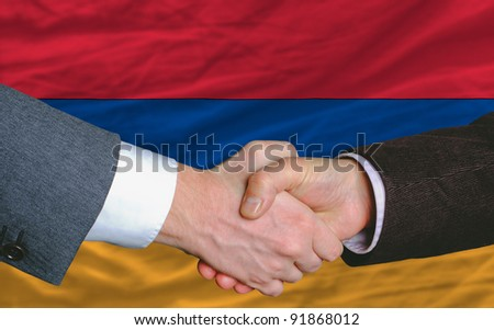 businessmen handshake after good deal in front of armenia flag - stock photo