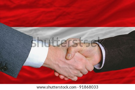 businessmen handshake after good deal in front of austria flag - stock photo