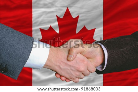 businessmen handshake after good deal in front of canada flag - stock photo