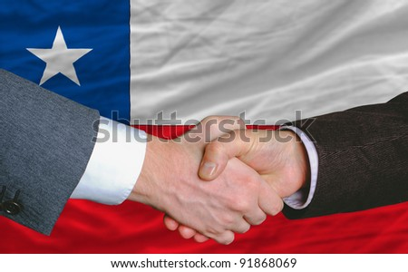 businessmen handshake after good deal in front of chile flag - stock photo