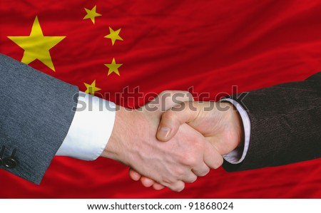 businessmen handshake after good deal in front of china flag - stock photo