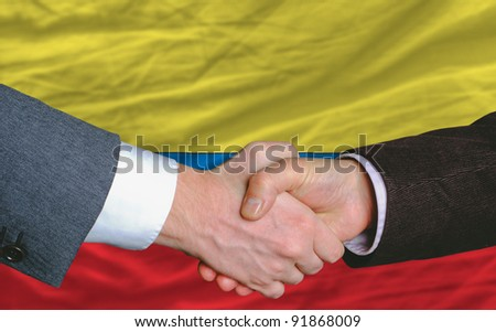 businessmen handshake after good deal in front of columbia flag - stock photo
