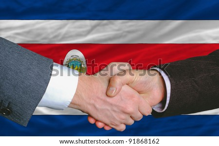 businessmen handshake after good deal in front of costa-rica flag - stock photo
