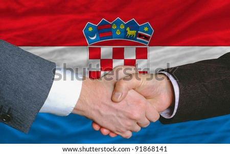 businessmen handshake after good deal in front of croatia flag - stock photo