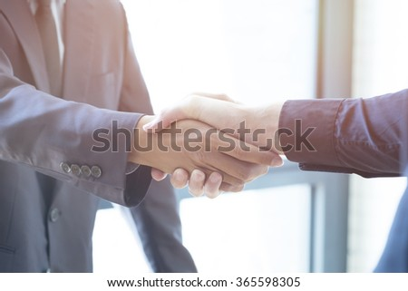 Businessmen handshake; success, dealing, greeting & business partner concepts - soft focus - stock photo