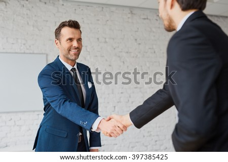 Businessmen handshaking after successful business meeting, negotiation - stock photo
