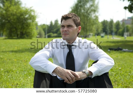 businessmen have relax in park sit on grass and look - stock photo