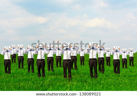 businessmen hiding their faces behind smile sing - stock photo