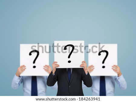 Businessmen holding question marks - stock photo