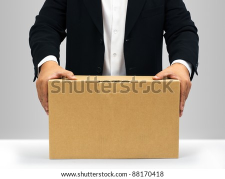 Businessmen in black suit Hold down on the brown paper box - stock photo