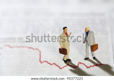 Businessmen in Conversation, two miniature models of businessmen in conversation standing over a red line graph . - stock photo
