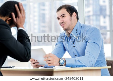 Businessmen in the negotiations. Two successful businessman sitting at the negotiating table in the office and communicate with each other. Business people dressed in formal wear - stock photo